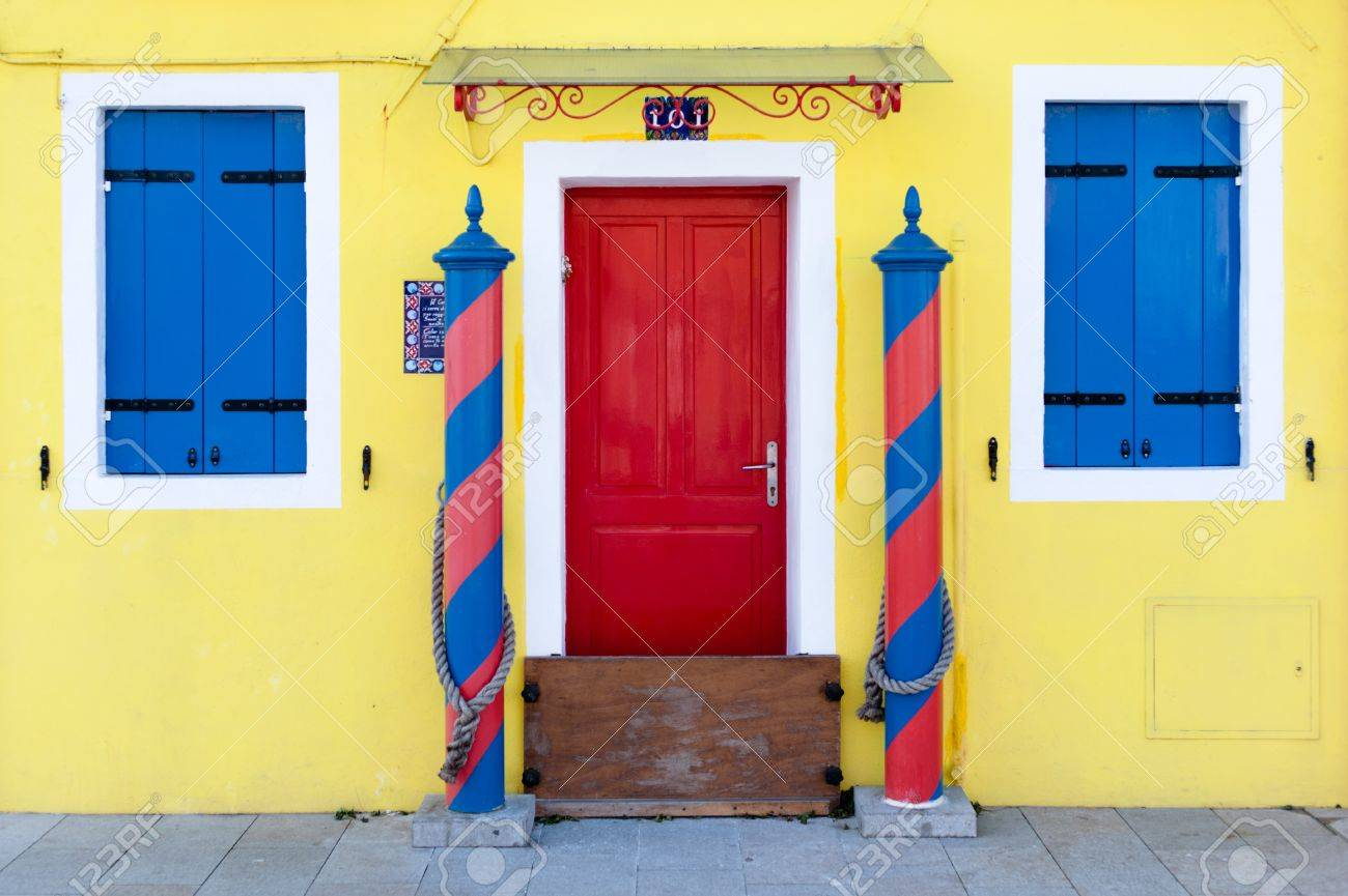 Colorful house entrance - bright yellow wall with blue windows and red door Stock Photo - 12528351