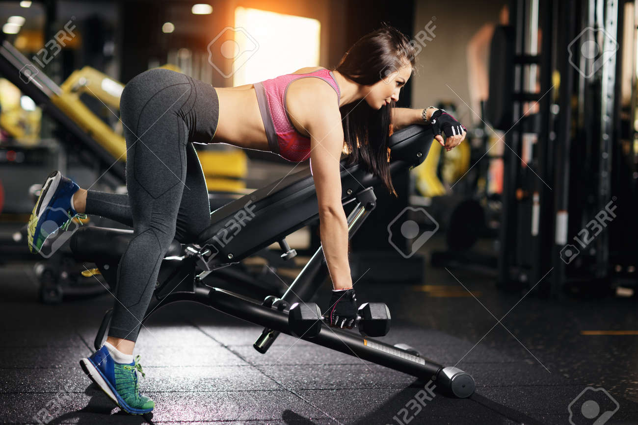 Young Fit Woman Doing Back Dumbbell Row Exercises On A Bench
