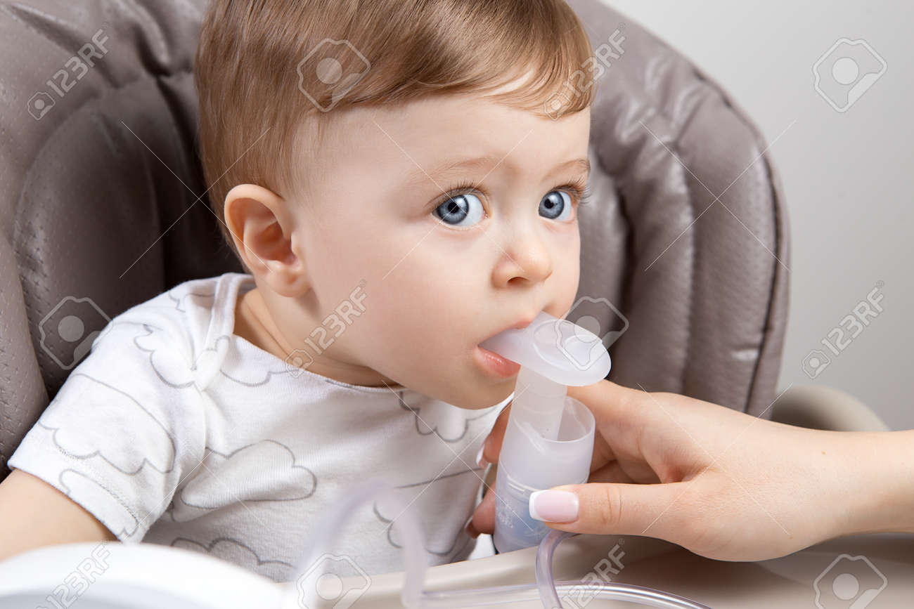 Mother Using Nebulizer For Cute Little Baby Boy Sitting On The
