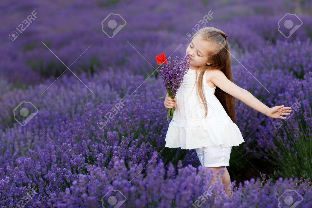 Happy Cute Little Girl In Lavender Field Holding Bouquet Of Purple ...