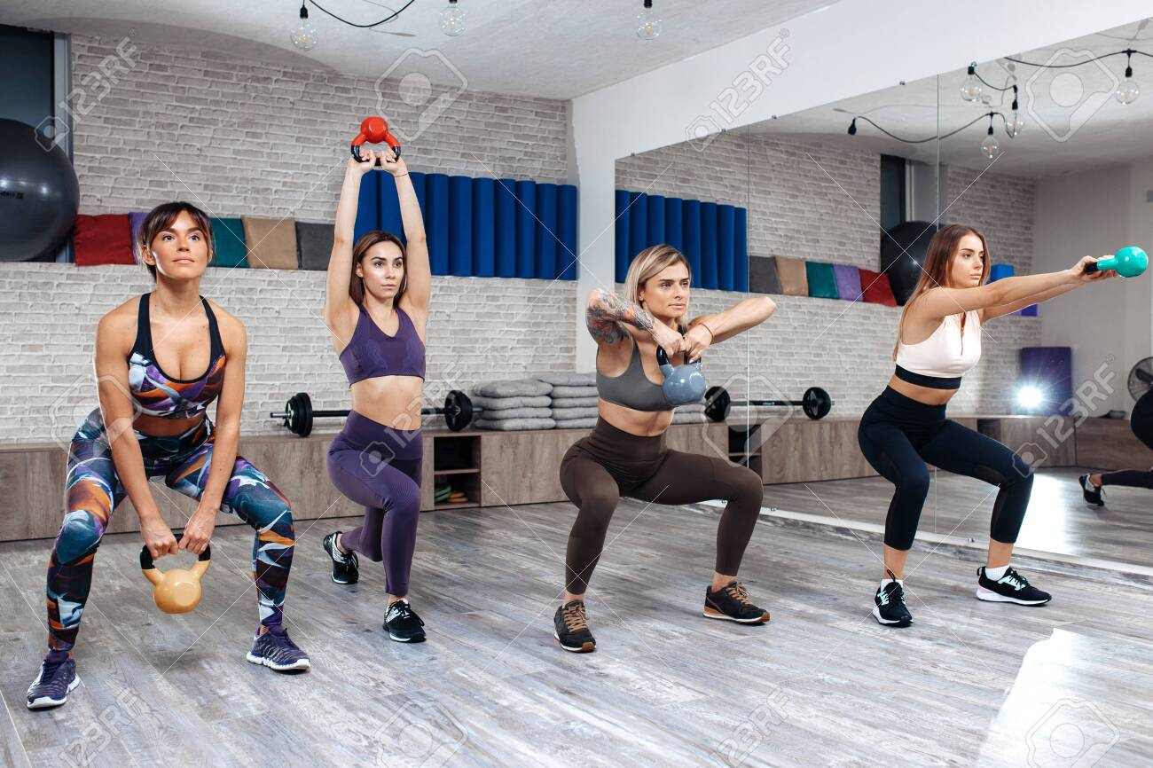 Group of four young sporty girls workout with kettlebells in fitness class. - 144476028