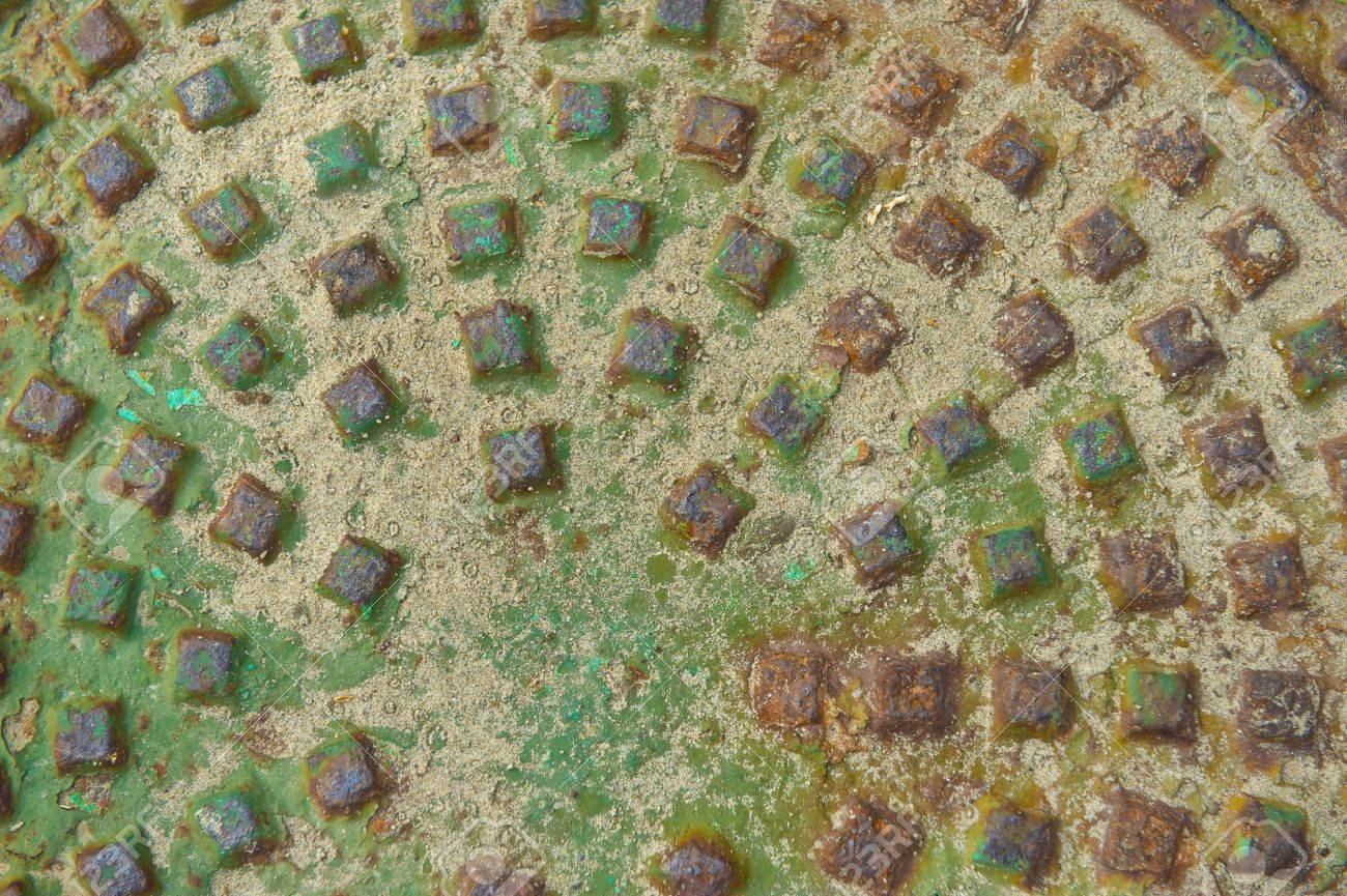 Oxidized man hole cover with rust stains and sand that includes a pattern of raised squares Stock Photo - 22550915