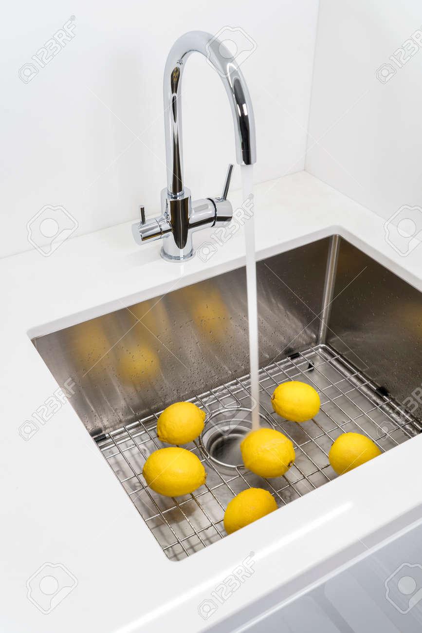 Washing lemons in the kitchen sink. - 142612518