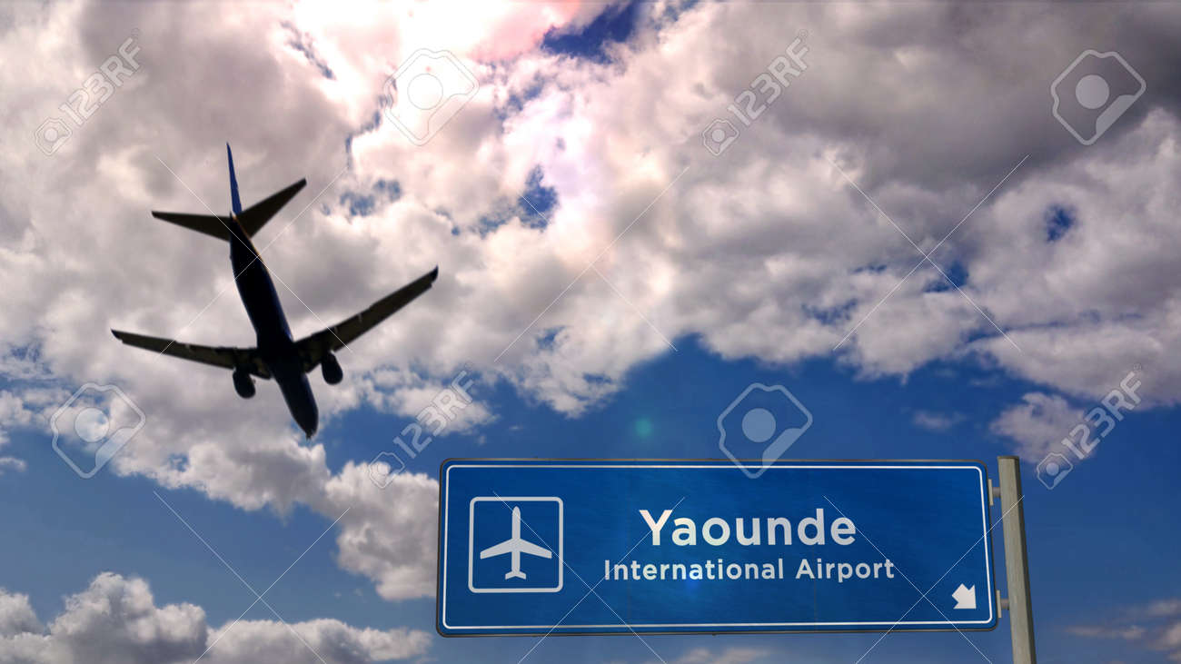 Jet plane landing in Yaounde, Cameroon. City arrival with airport direction sign. Travel, business, tourism and transport concept. 3D rendering. - 170077435