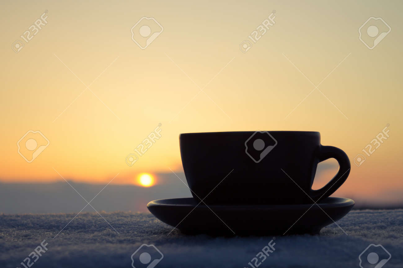 Romantic winter evening Cup of coffee or tea in rays of sunset - 18776655