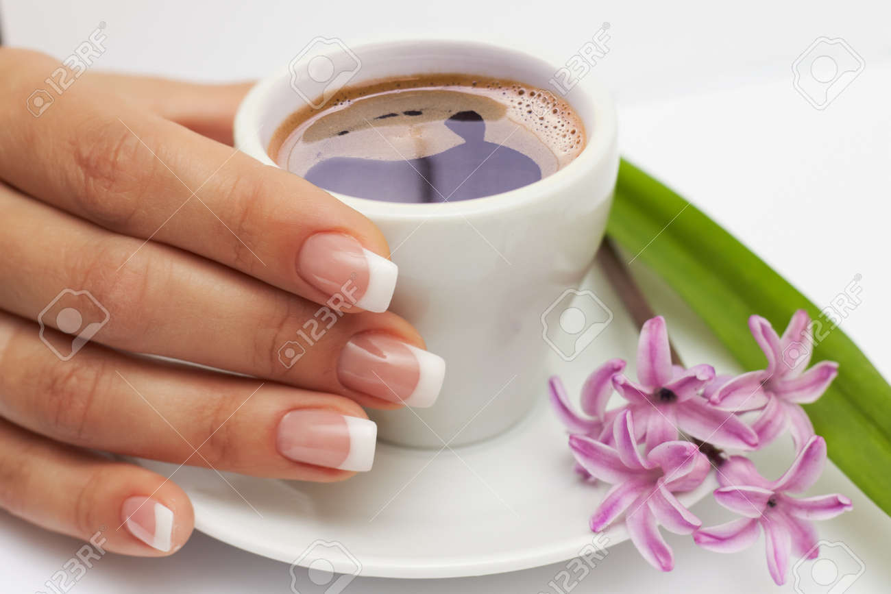 Beautiful manicured hand with french nails and cup of coffee and flowers at saucer on white background - 19089230