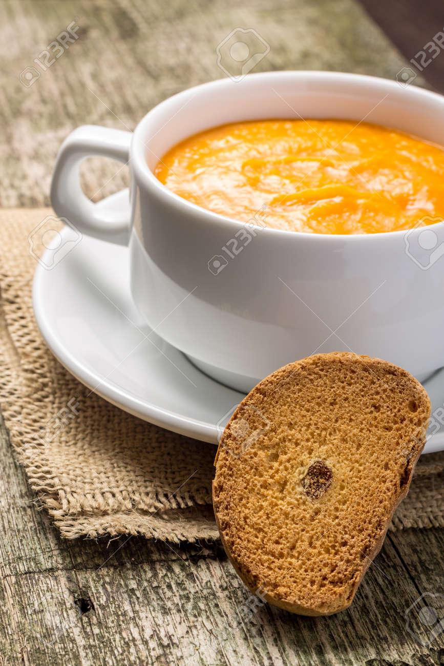 Pumpkin soup at old wood plank - 22022534