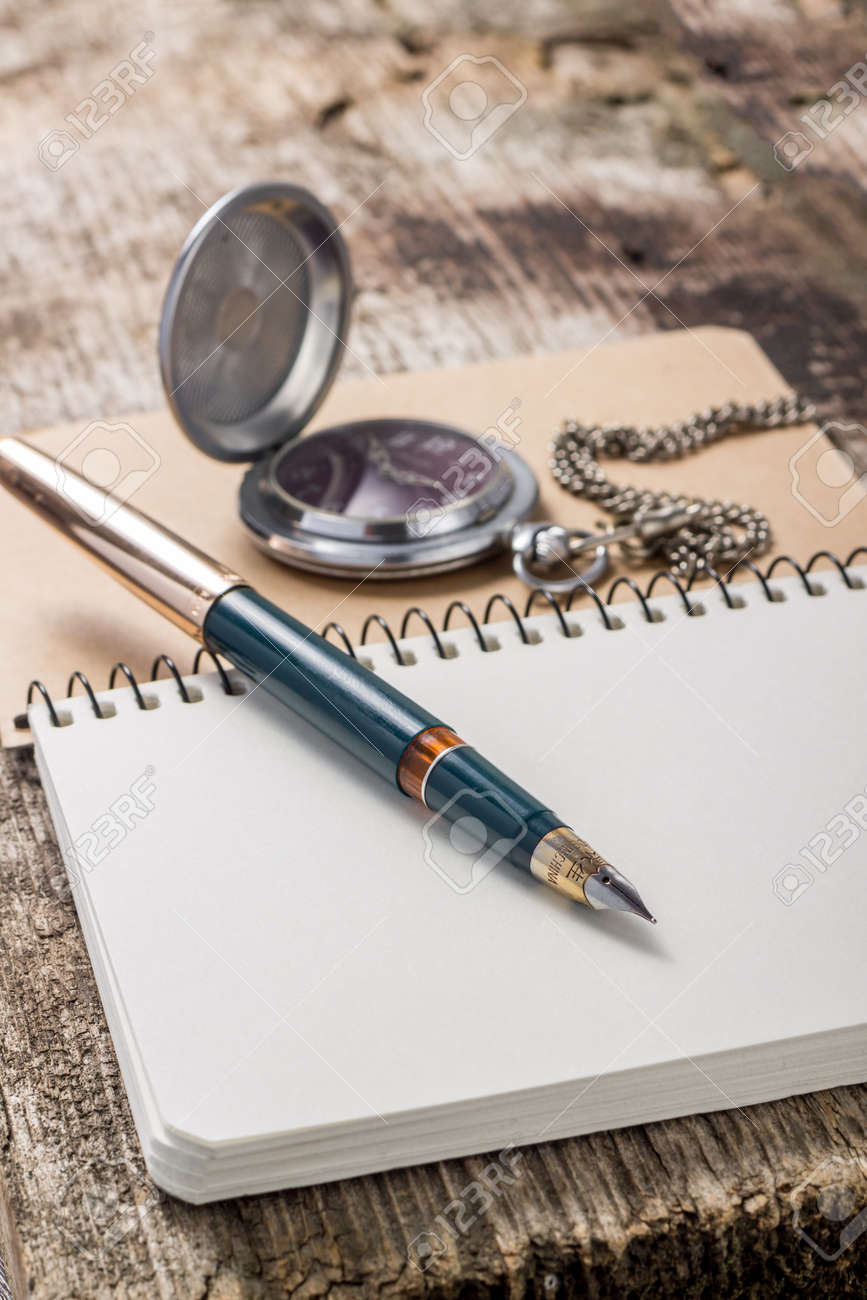 Golden in pen with pocket watch at white notebook - 22269132