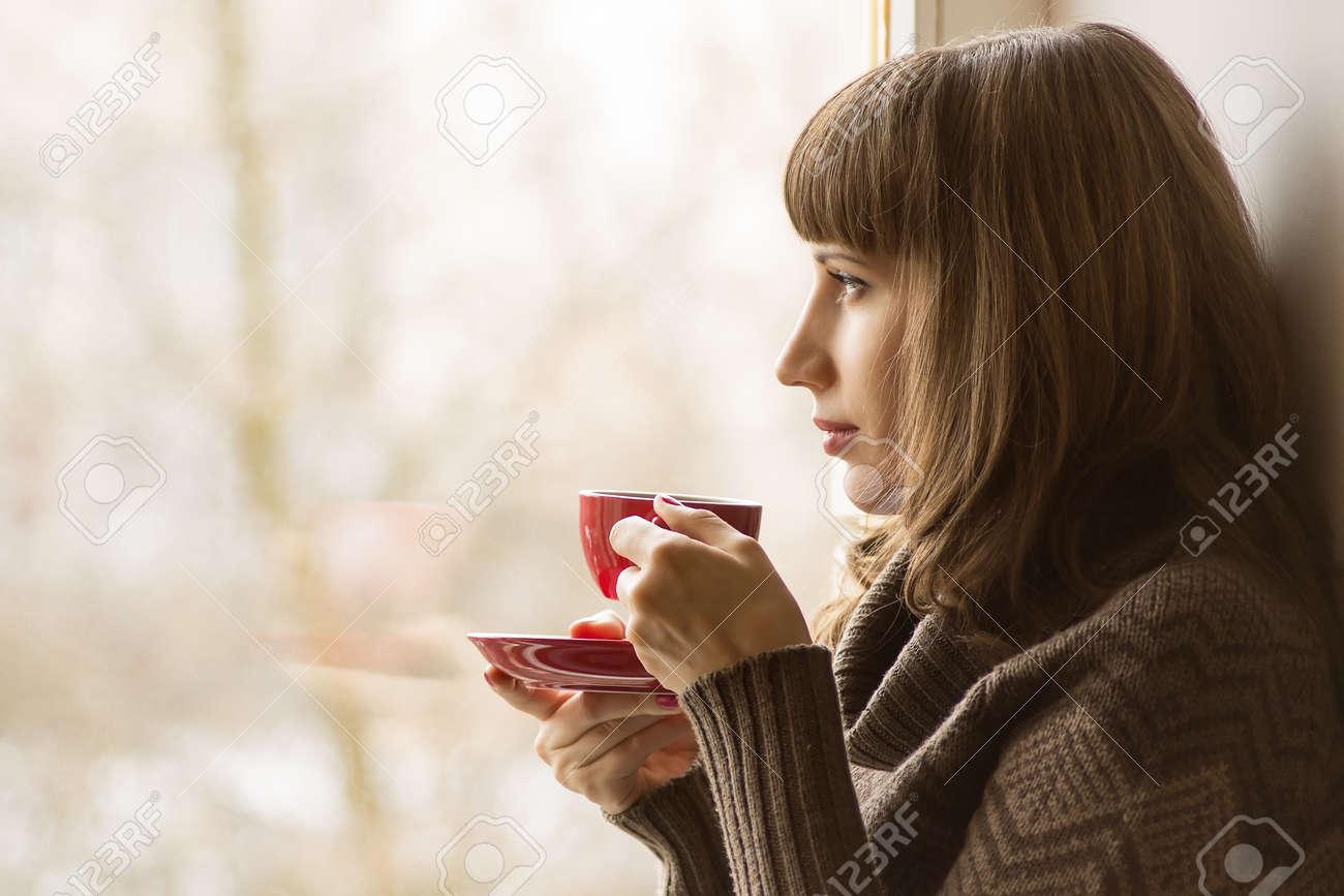 Beautiful girl drinking Coffee or Tea near Window - 25408499