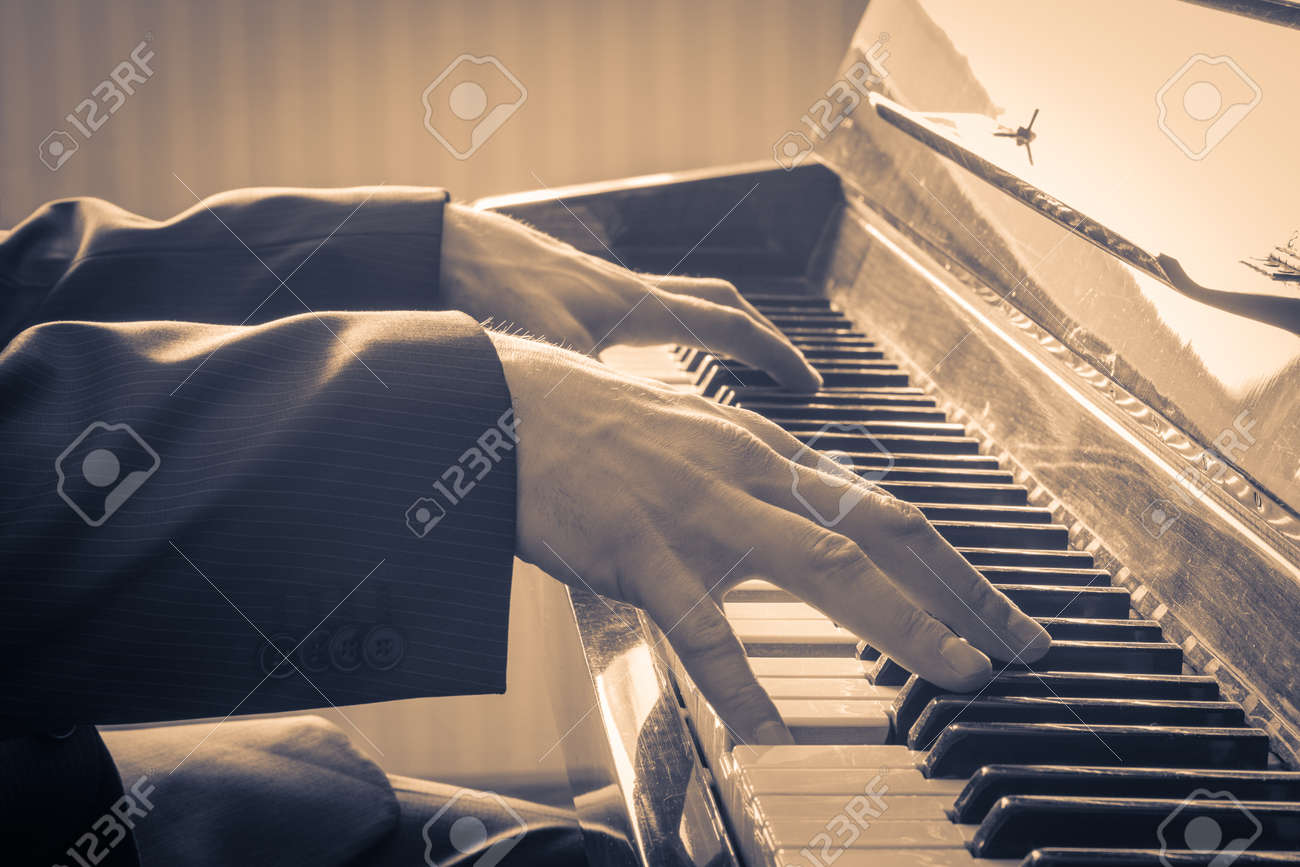 Man's hands playing the Piano. Retro Style. Warm color toned - 26976717