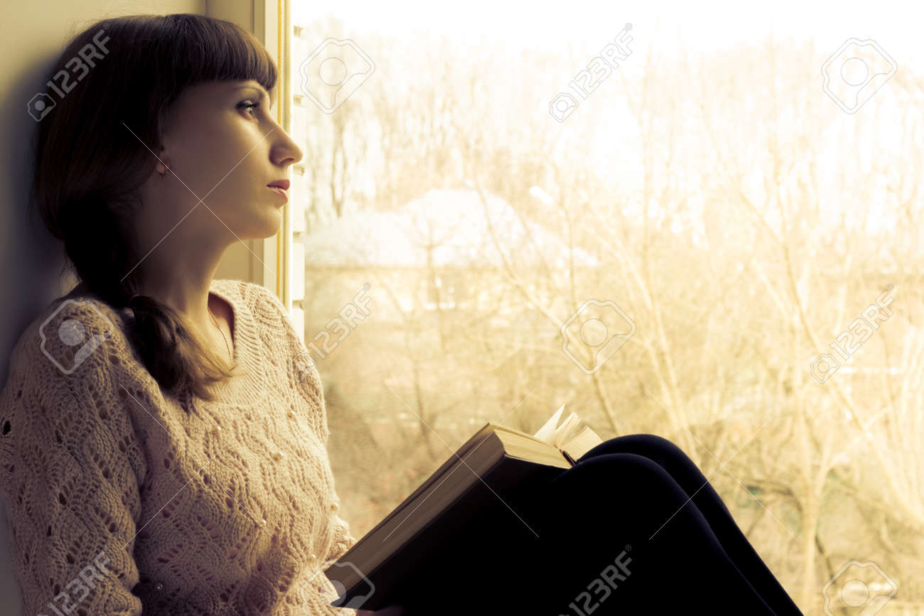 Young woman reading book near the window. Warm toned image - 27096350