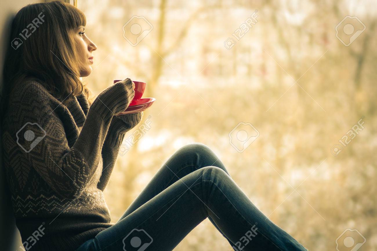 Beautiful girl dreaming with cup of coffee or tea near window - 27115492