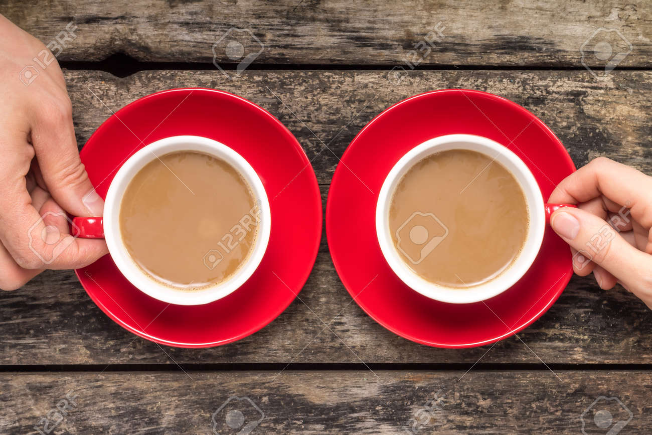 Hands taking cup of coffee on wood background - 27750241