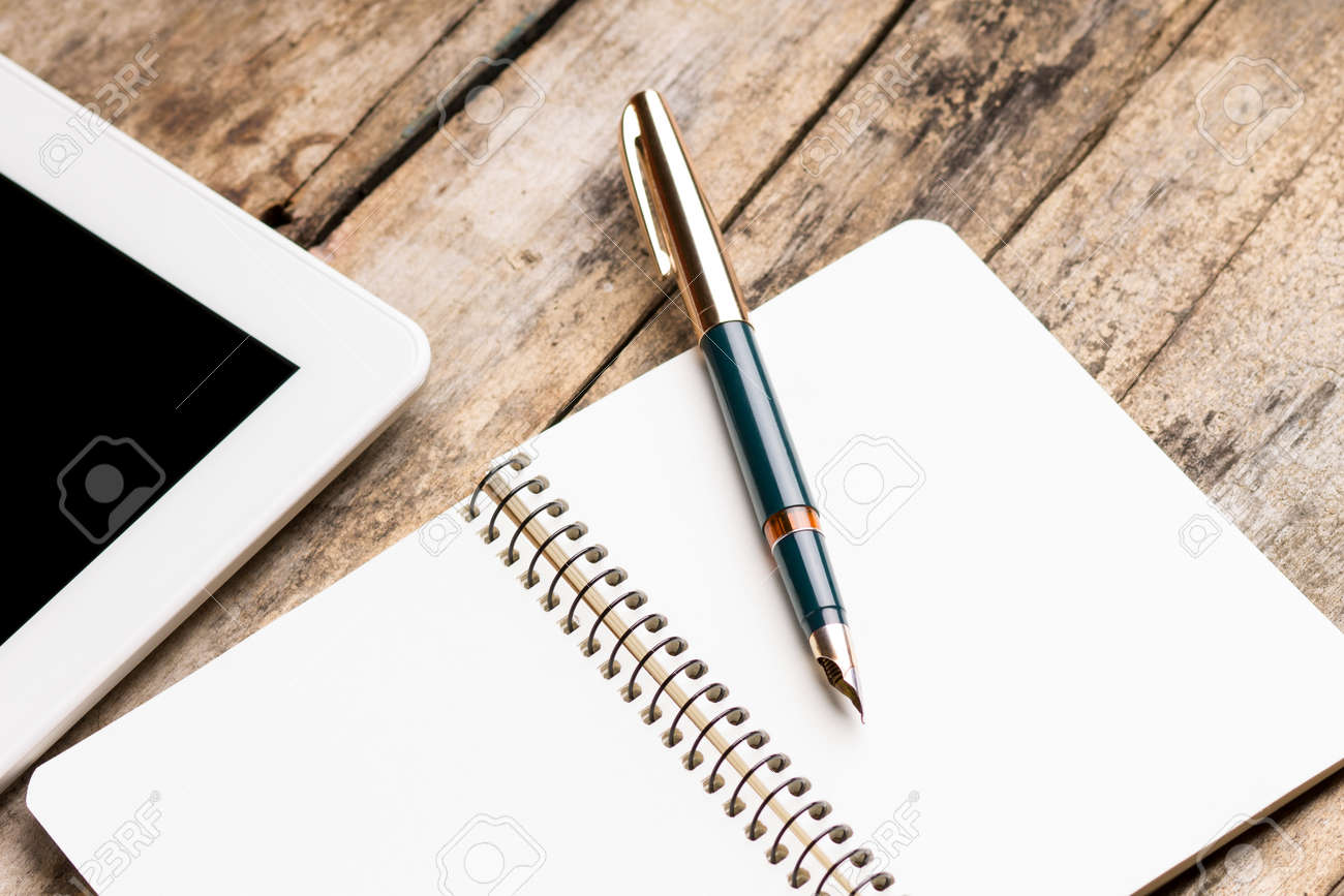 Digital tablet with empty notebook and old fountain pen on rustic wooden table. - 35404456
