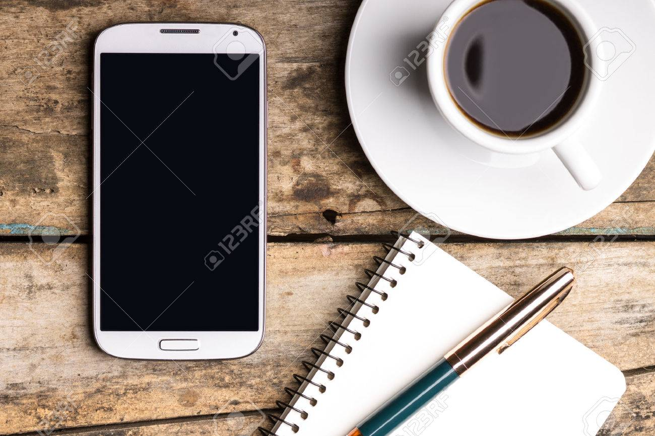 Smartphone with notebook and cup of strong coffee on wooden background. Cell phone with writing set with espresso - 36197295