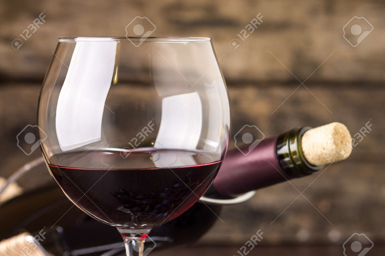 Red wine in wineglass against corked bottle on wood background - 37141095