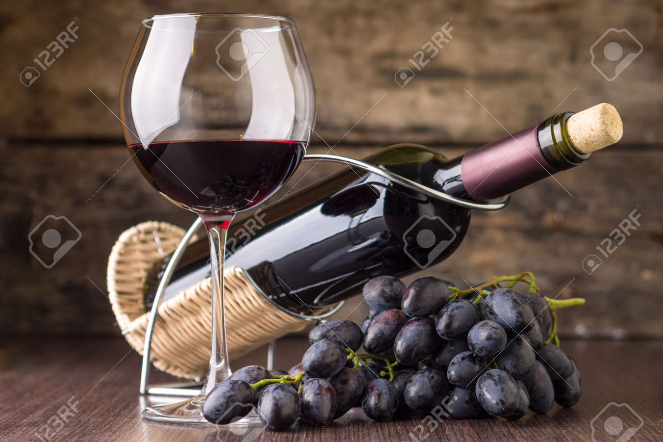 Winery background. Elegant wineglass with bottle of red wine and cluster of grape. - 37141096
