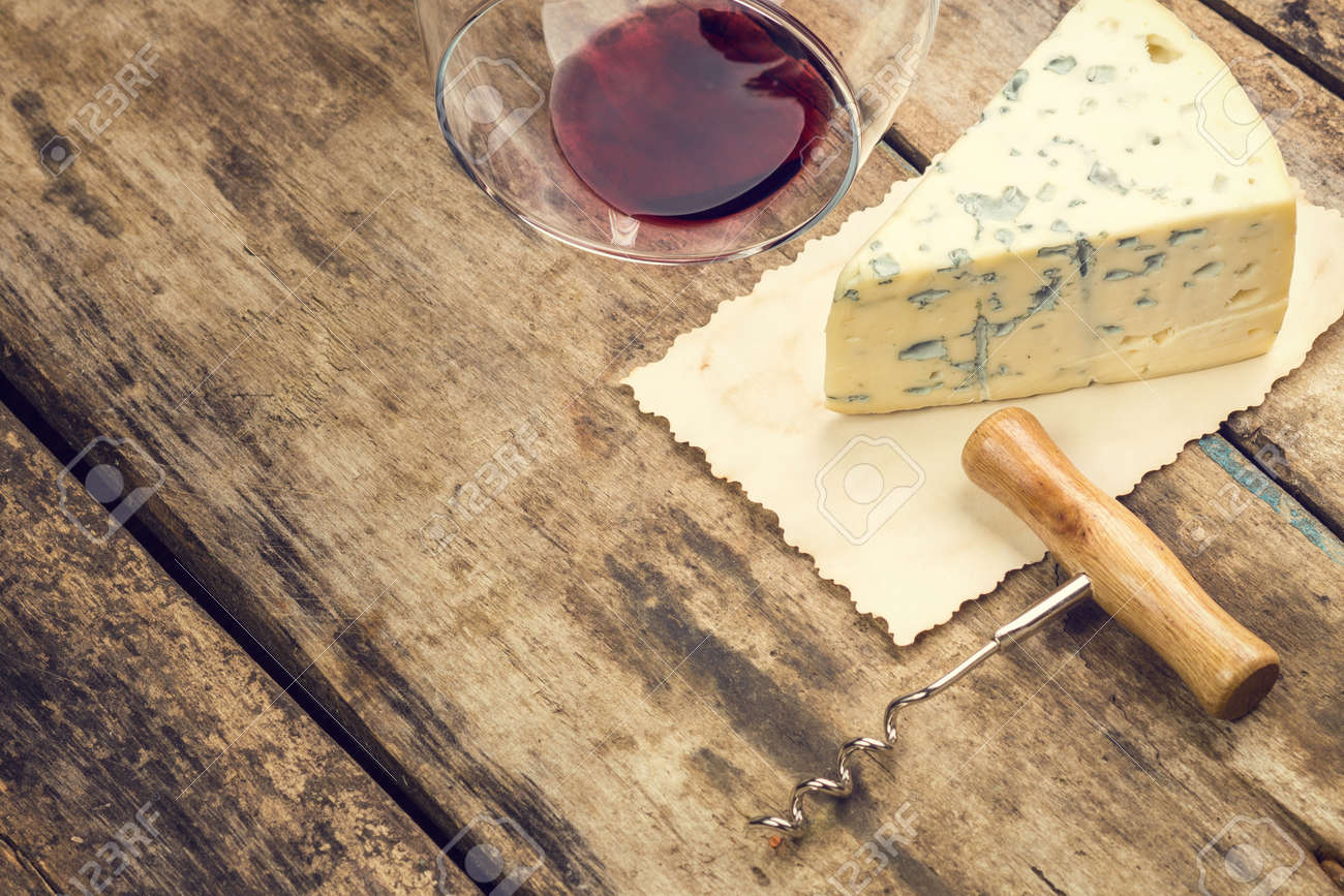 Blue cheese on vintage paper sheet with overturned wine glass and corkscrew. Warm color toned image with copyspace. - 39101992