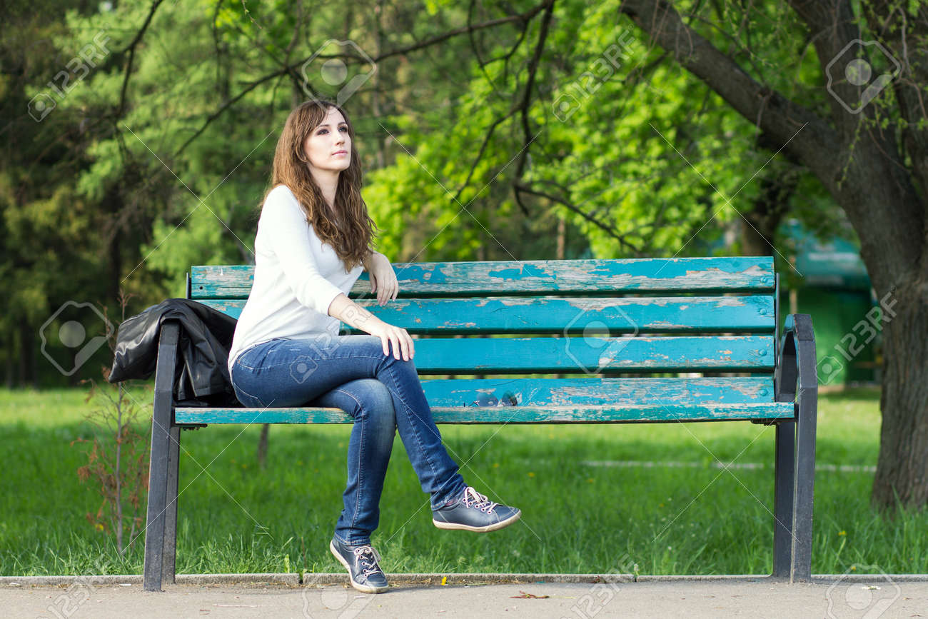 Young beautiful woman sitting on bench in park. Pretty girl at outdoors on summer day. Nature environment background. - 40614995