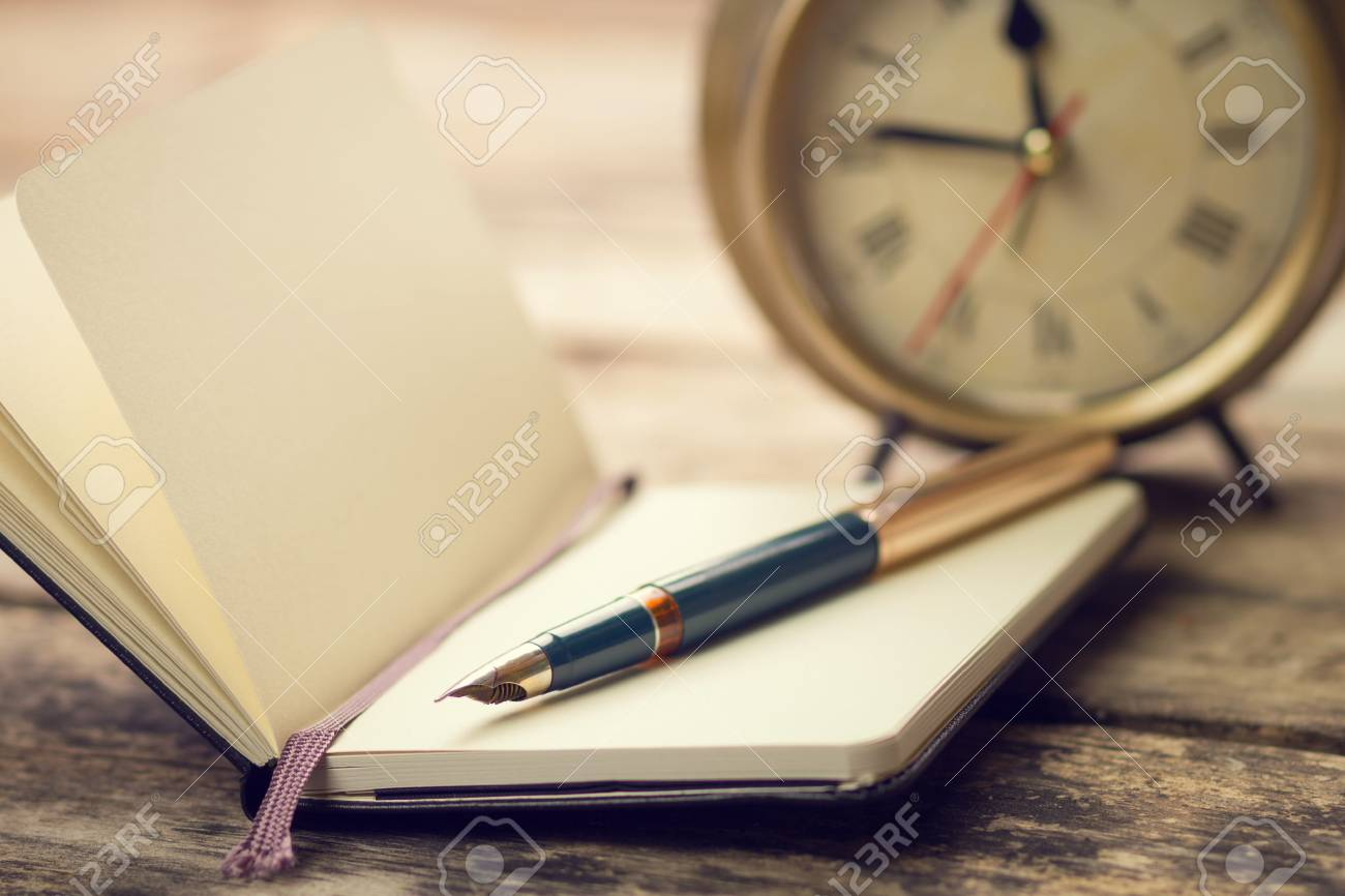 Open small notebook with fountain pen and old-fashioned alarm clock behind. Warm color toned vintage image - 43649148