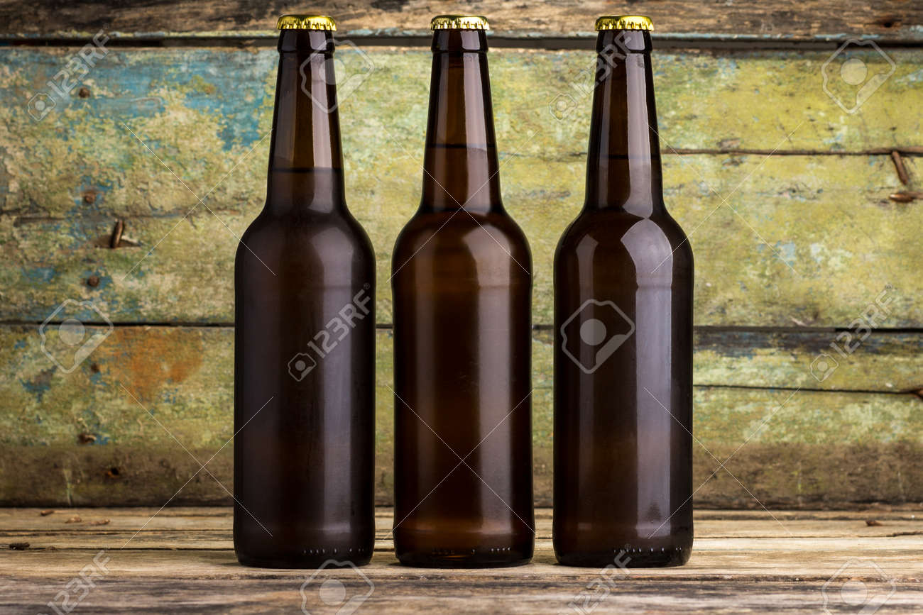 Three bottles of beer against wooden background - 46048080
