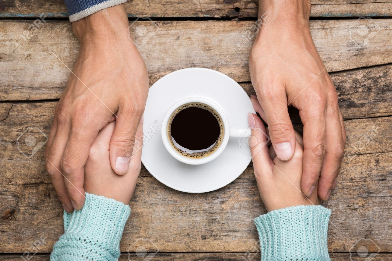 Man holds woman's hand near a cup of coffee top view image on wooden backdrop. Friendship coffee background - 47197585
