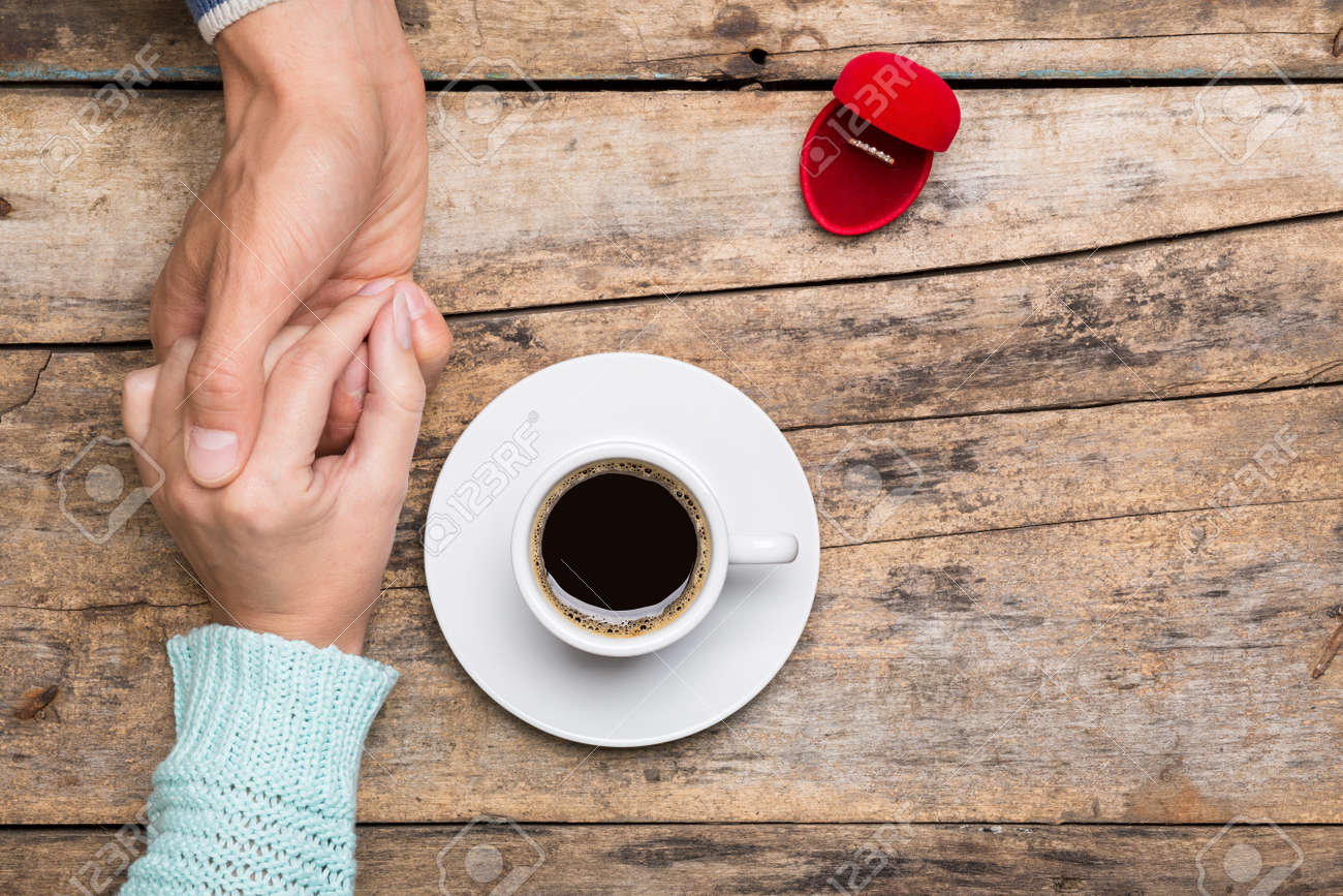 Man holds woman's hand and gives a ring in red box for present. Coffee break dating gift - 47197643
