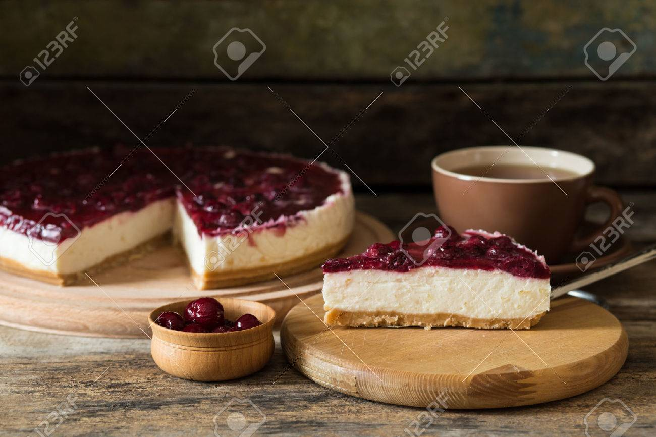 Slice of cheesecake with cherry and cup of tea on wooden background - 50862198
