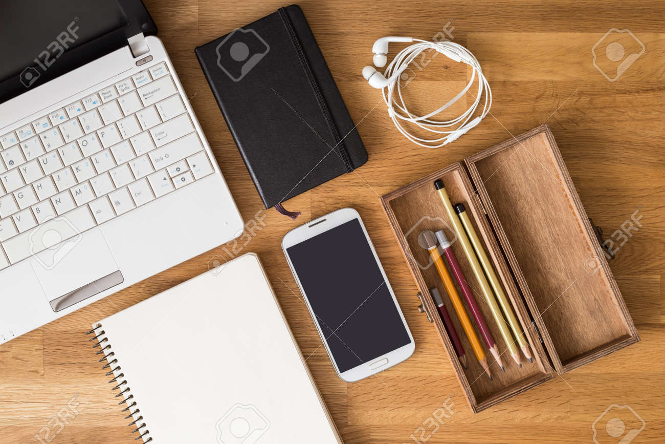 https://previews.123rf.com/images/skumer/skumer1603/skumer160300140/55999932-mock-up-of-student-desk-with-laptop-note-phone-and-pencils-in-wooden-box-top-view-image-of-designer-.jpg