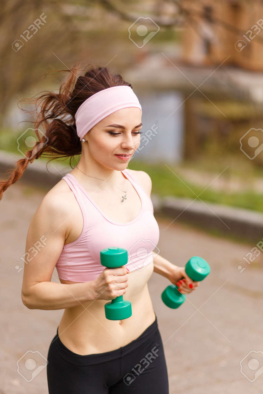 Young athletic woman jogging with dumbbells in park. Smiling girl in sportswear running on pathway - 57241857