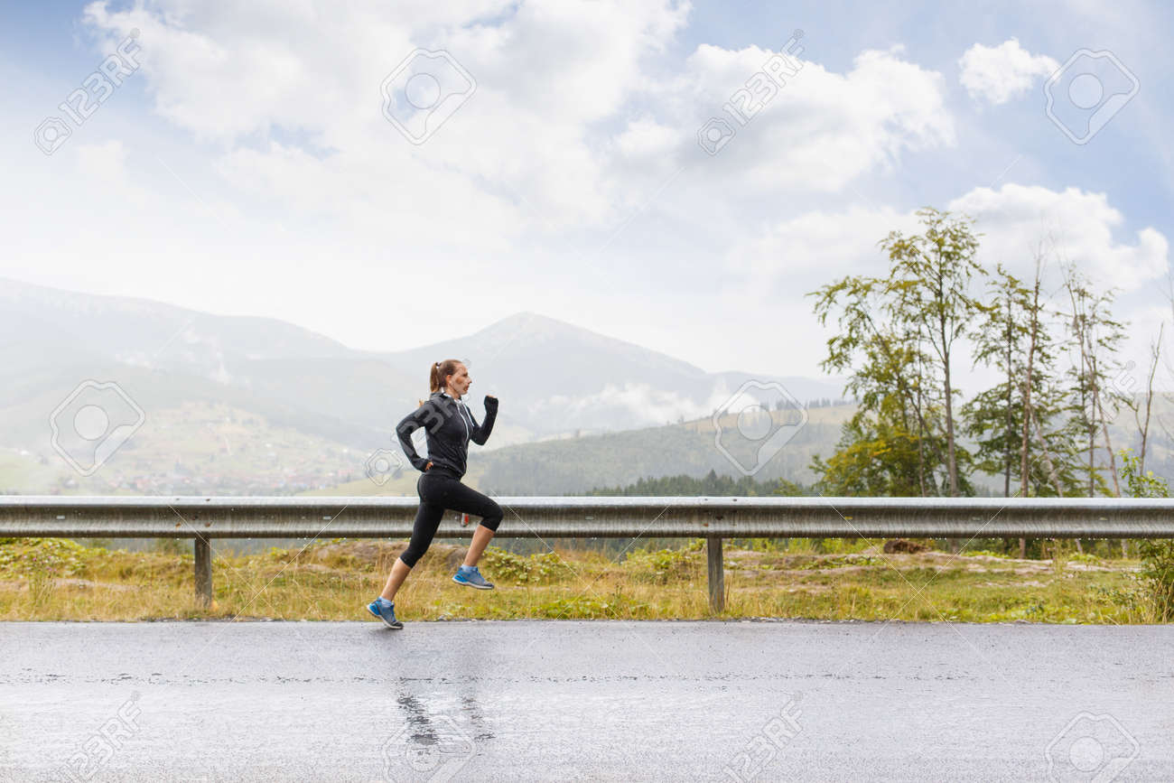 Young female runner on rainy road in mountains. Athletic girl jogging at the morning - 64327475