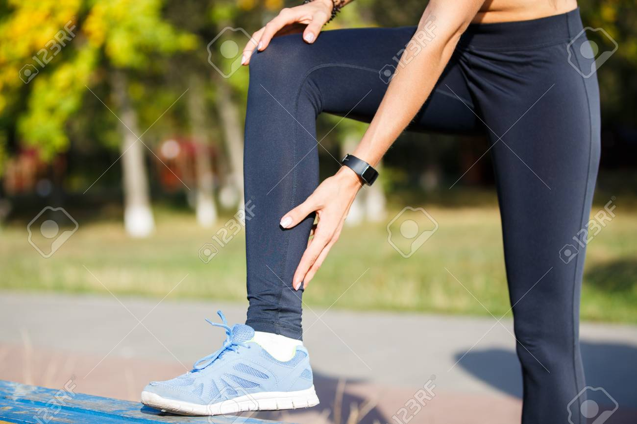 Female runner touching cramped calf at morning jogging. Achilles tendon pain or injury concept background - 88043254