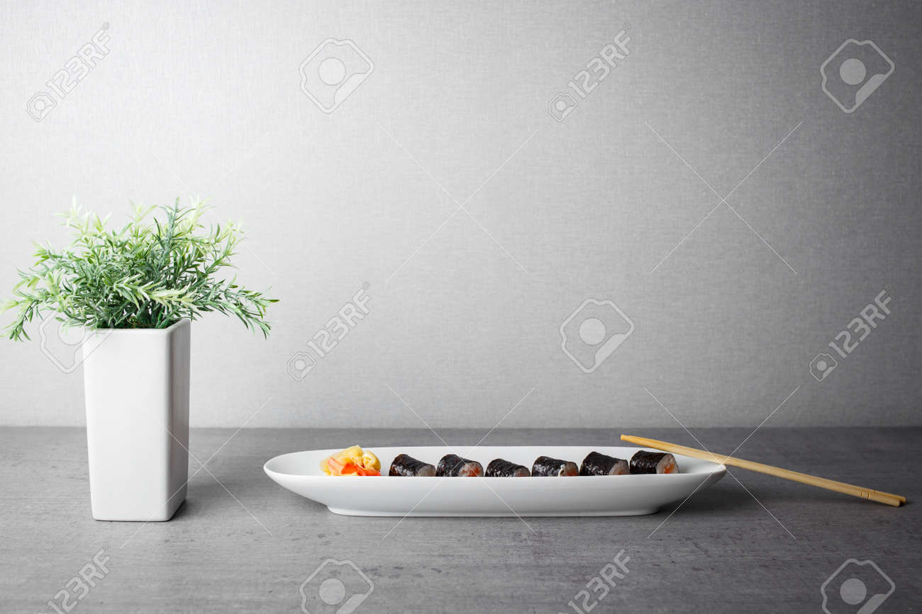 Maki sushi served in long plate on grey table - 115521390