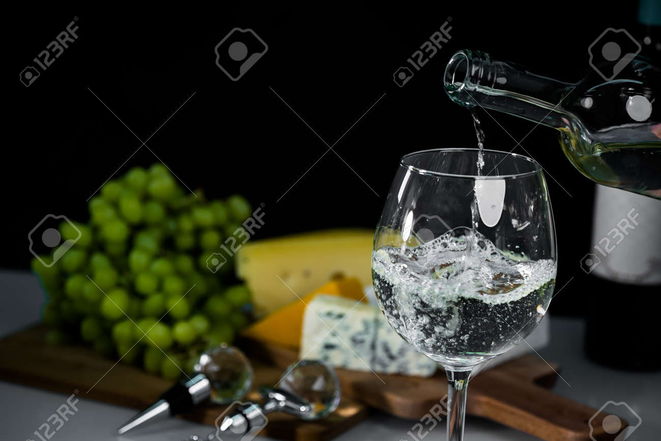Cropped view sommelier pouring wite wine from bottle into glass - 142549802