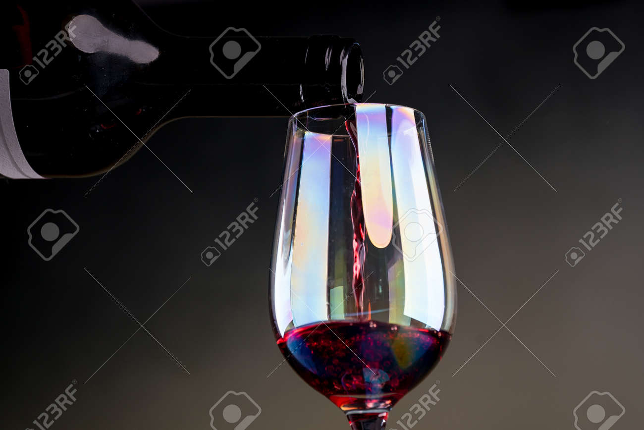 Cropped view sommelier pouring red wine from bottle into glass - 142549809