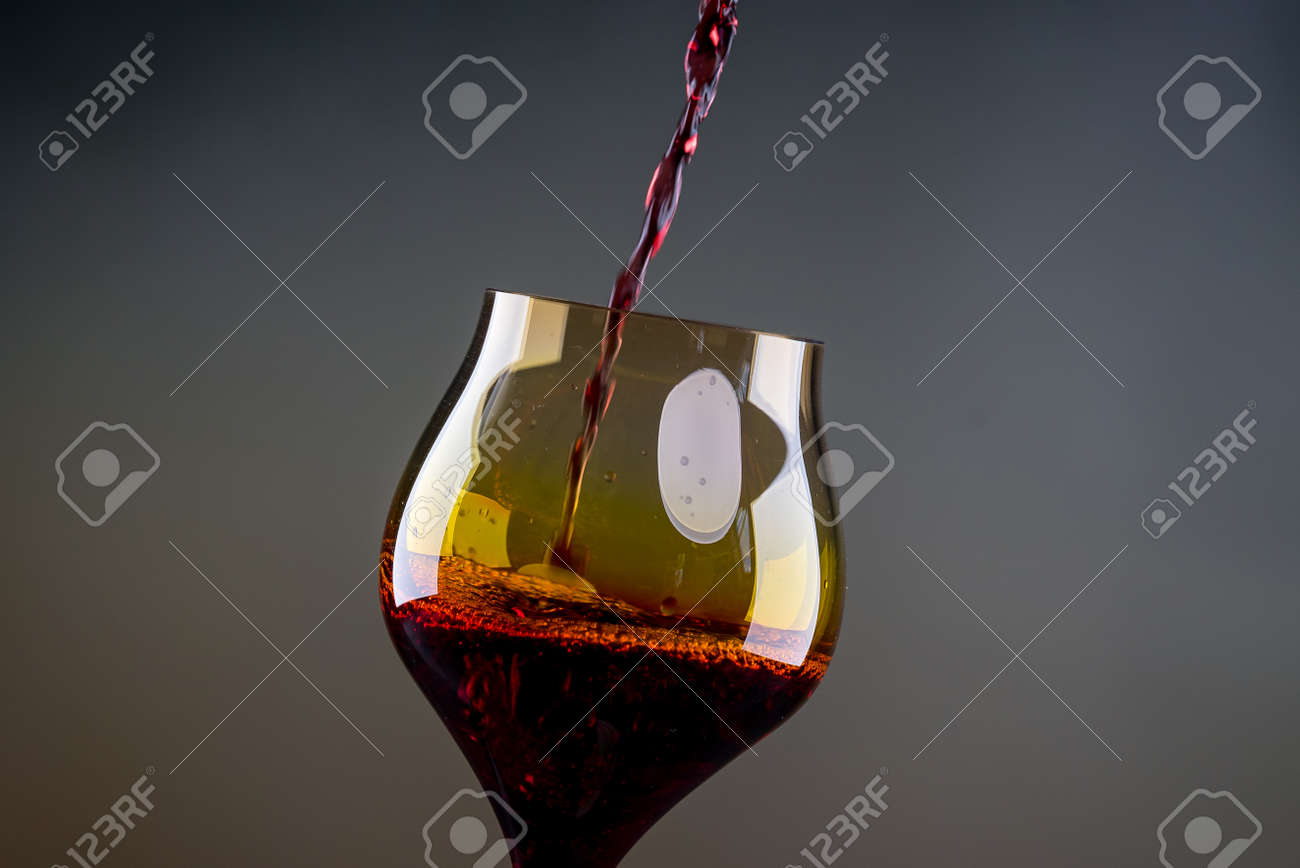 Red wine being poured into a glass close-up - 142549811