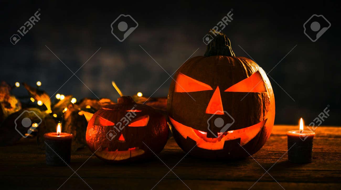 Halloween pumpkin head jack lantern with burning candles in scary deep night - 141470803