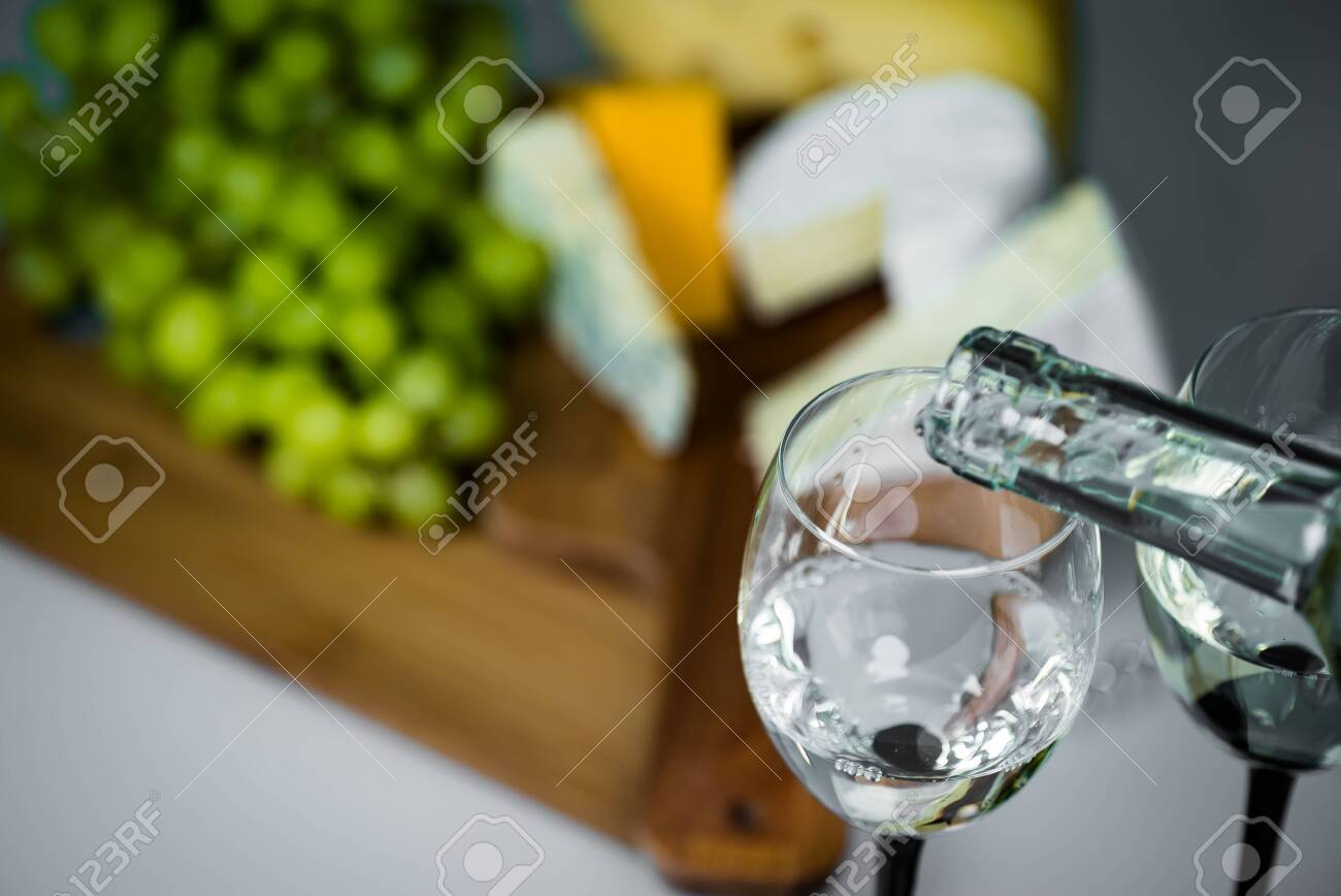 White wine being poured into a glass close-up - 142549820
