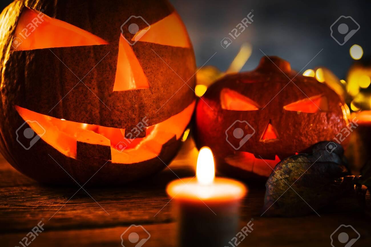 Halloween pumpkin head jack lantern with burning candles in scary deep night - 141470806