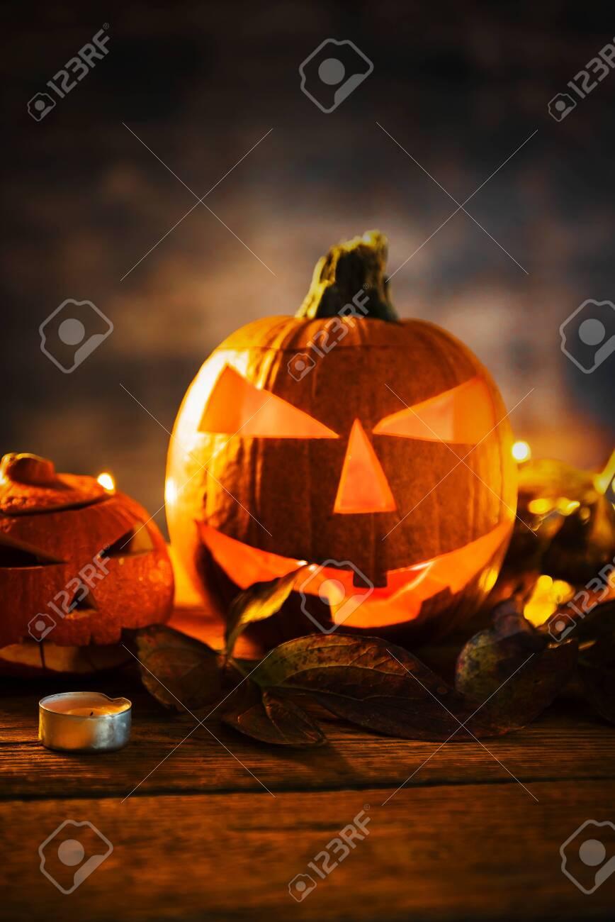 Halloween pumpkin head jack lantern with burning candles in scary deep night - 141470811