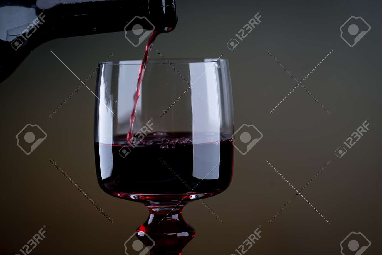 Red wine being poured into a glass close-up - 142549027