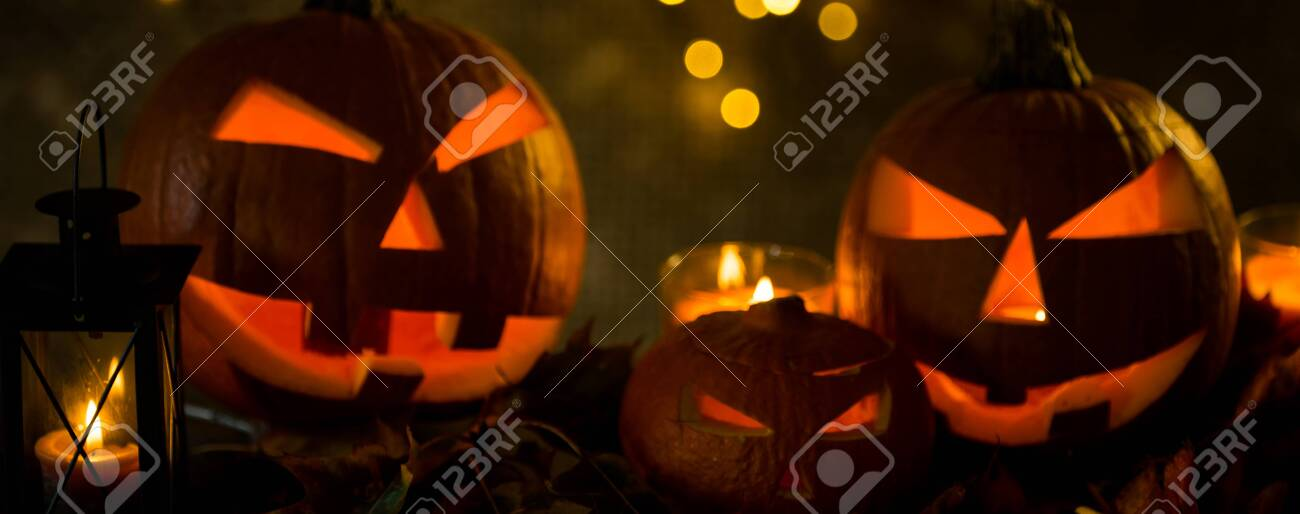 Halloween pumpkin head jack lantern with burning candles in scary deep night - 141470823