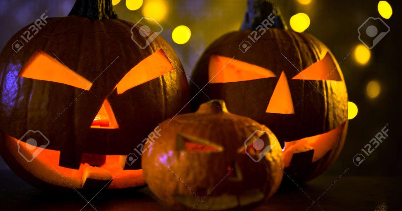 Halloween pumpkin head jack lantern with burning candles in scary deep night - 141470825