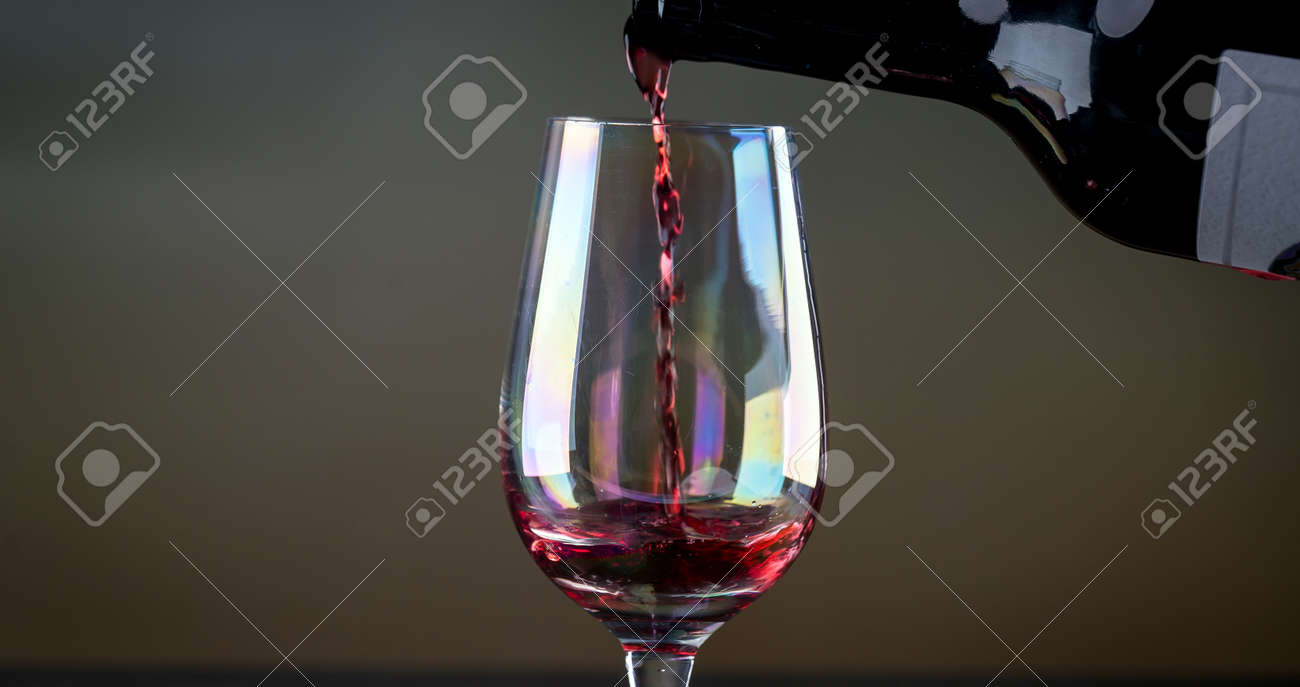 Red wine being poured into a glass close-up - 142548079