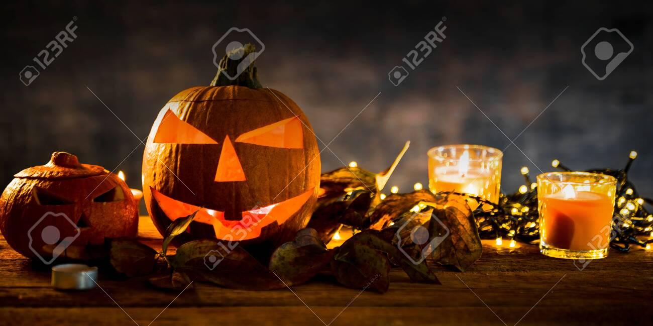 Halloween pumpkin head jack lantern with burning candles in scary deep night - 141470900