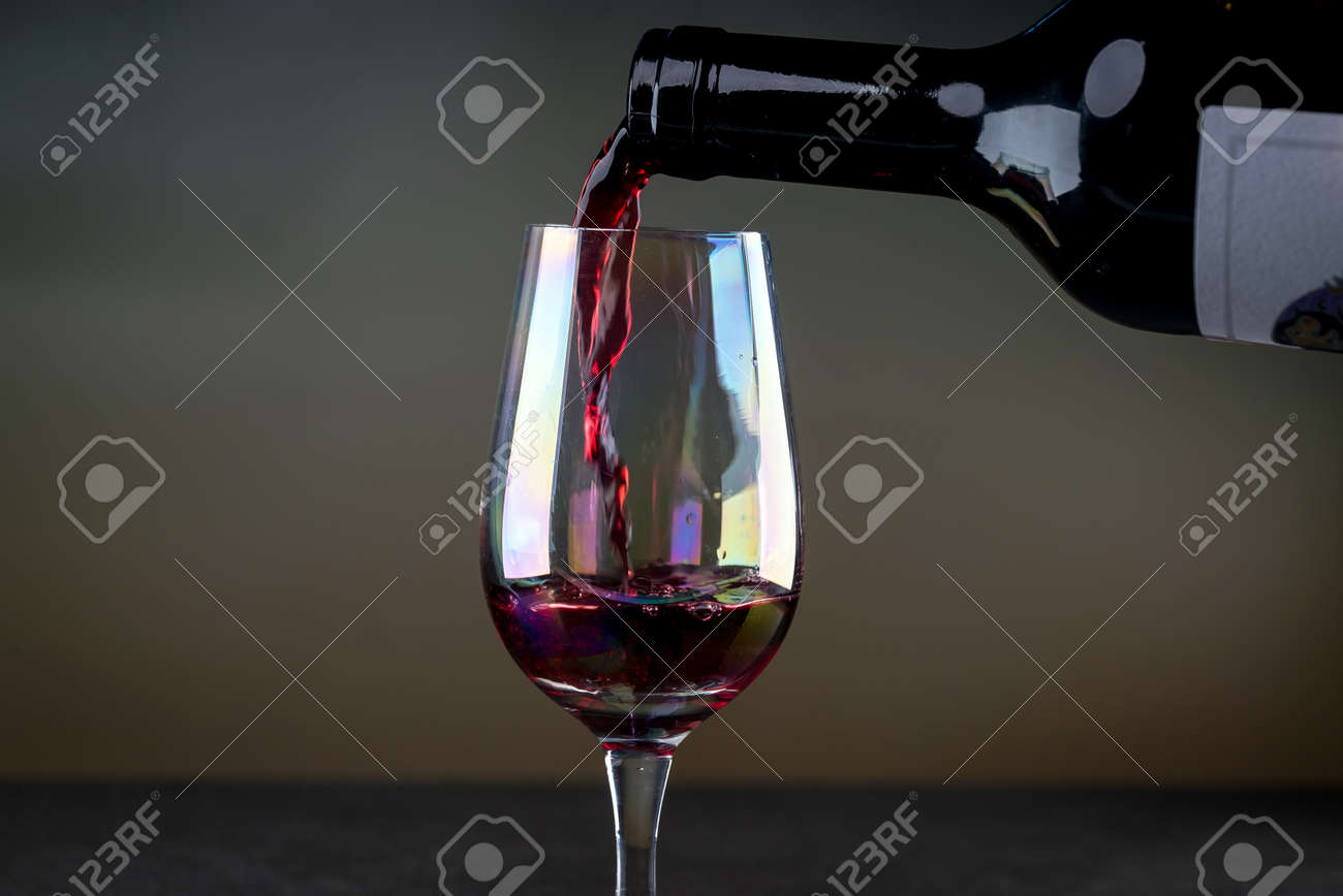 Red wine being poured into a glass close-up - 142548086