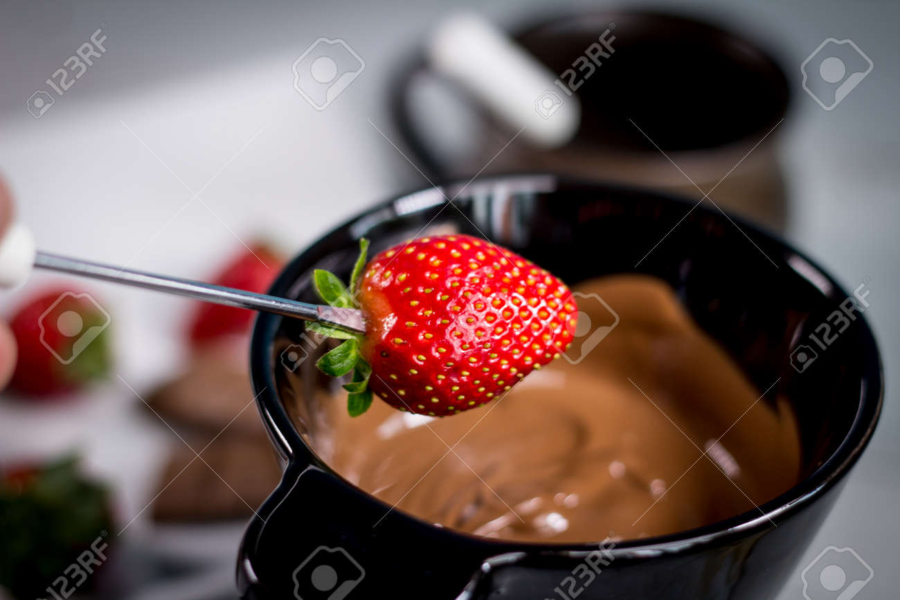 Chocolate fondue with fresh berries on wooden table - 144316078