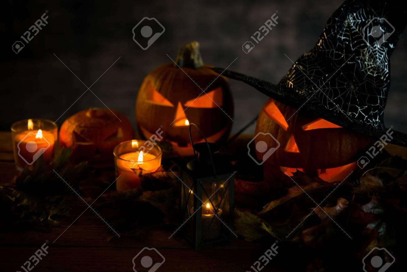 Halloween pumpkin head jack lantern with burning candles in scary deep night - 141470942