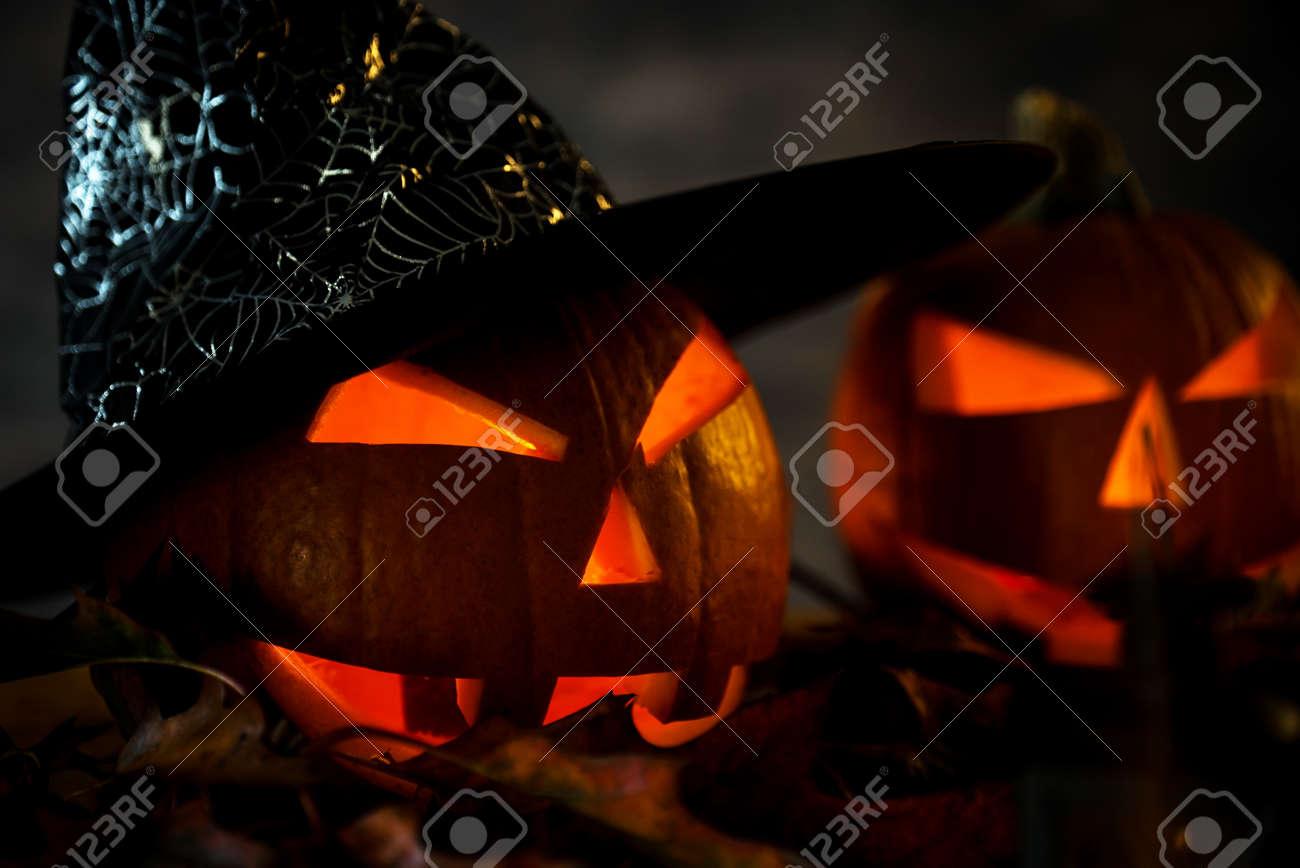 Halloween pumpkin head jack lantern with burning candles in scary deep night - 141470944