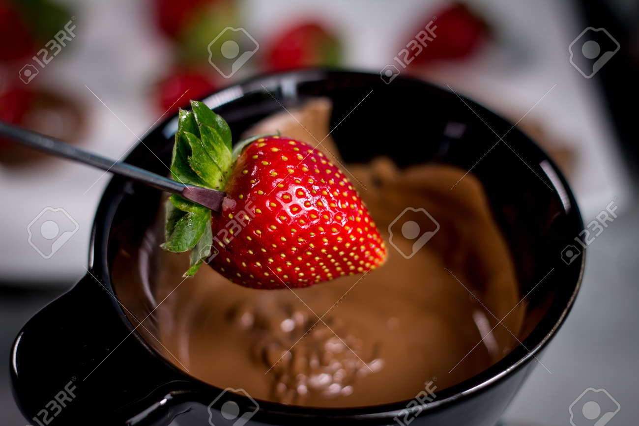 Chocolate fondue with fresh berries on wooden table - 144316090